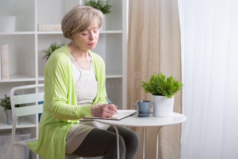 Reife Frau, die im Kalender merkt lizenzfreies stockbild