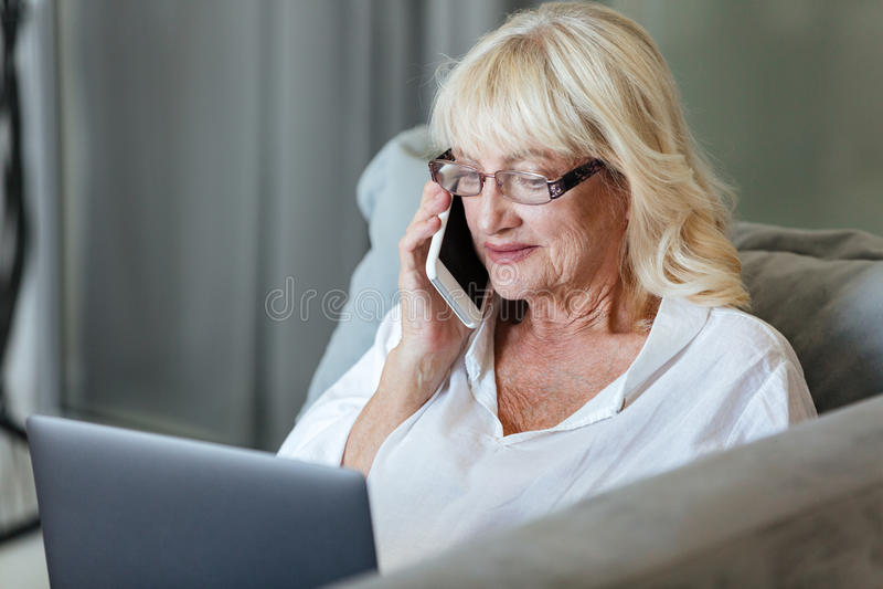 Reife Frau, die Laptop-Computer verwendet stockbild