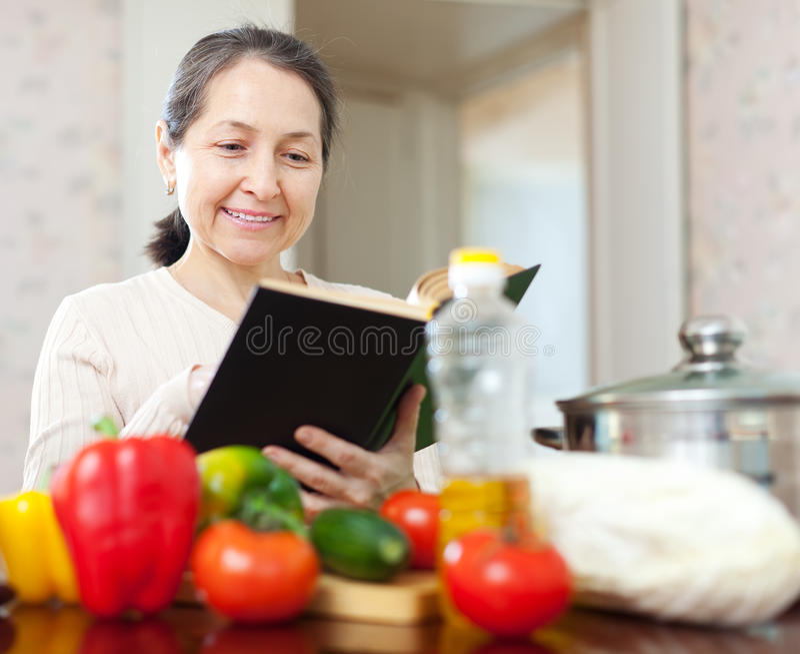 Reife Frau, die mit Kochbuch kocht lizenzfreies stockbild