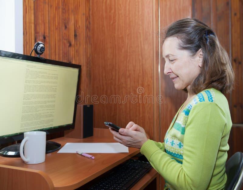 Reife Frau, die nahe Computer arbeitet stockbild
