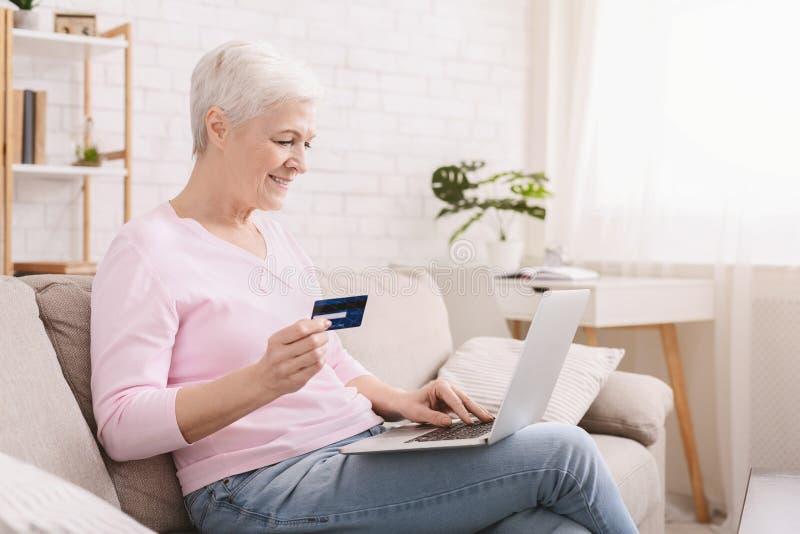 Reife Frau, die online mit Kreditkarte und Laptop kauft lizenzfreie stockfotos