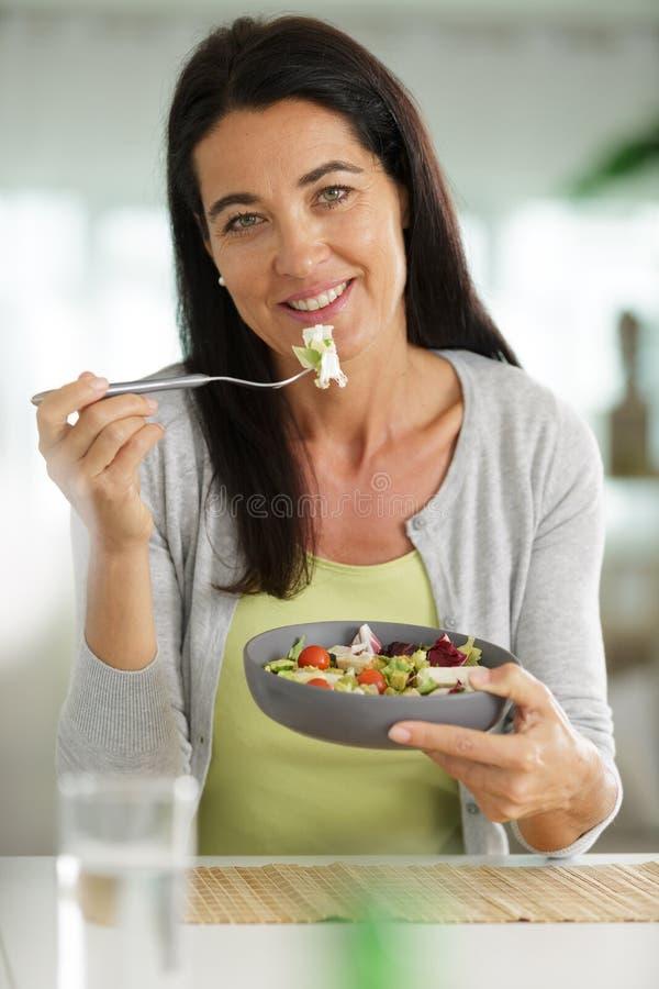 Reife Frau, die Salat isst stockfotografie