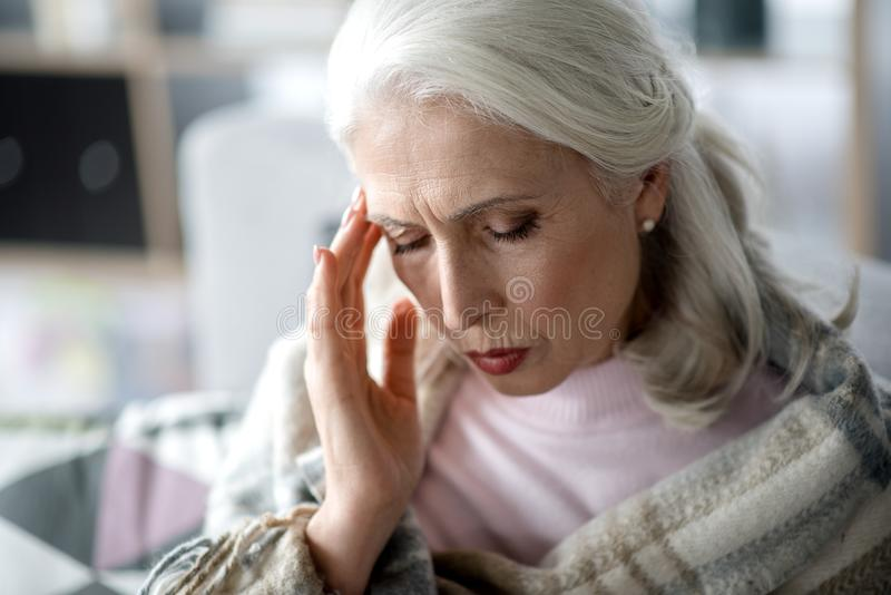 Reife Frau, die unter Kopfschmerzen leidet lizenzfreie stockbilder