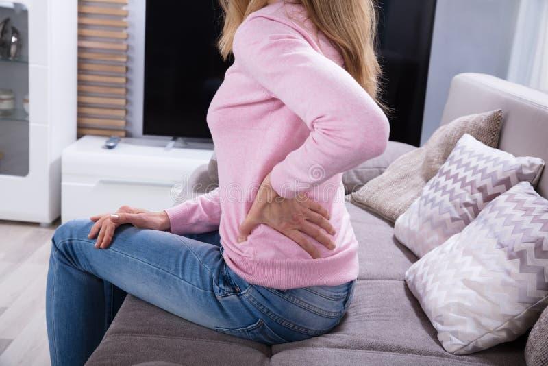 Reife Frau, die unter Rückenschmerzen leidet stockbild
