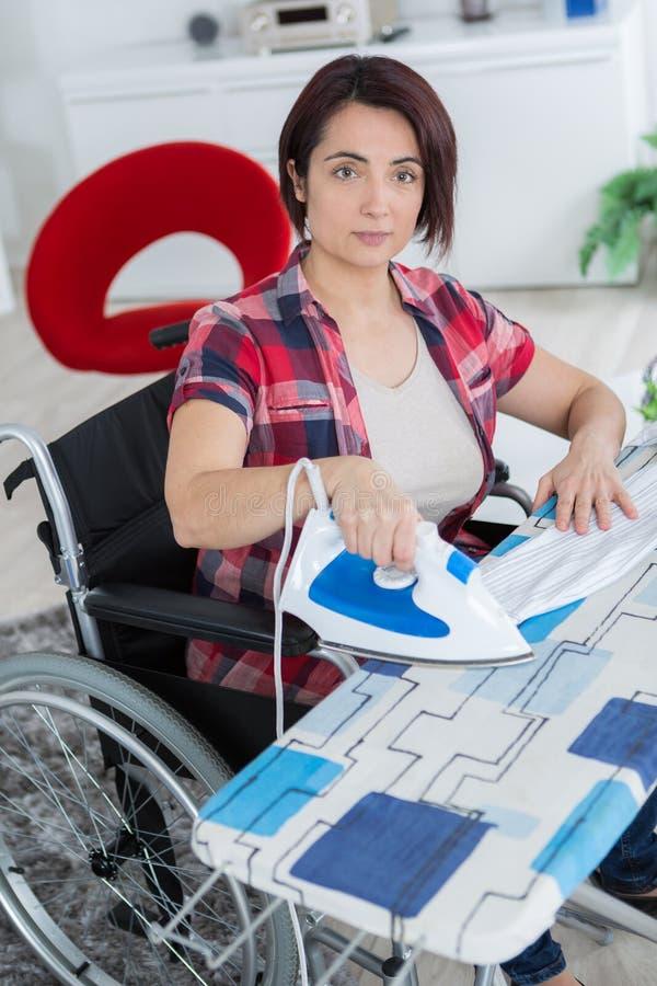 Reife Frau, die zu Hause beim Sitzen auf Rollstuhl bügelt lizenzfreie stockfotos