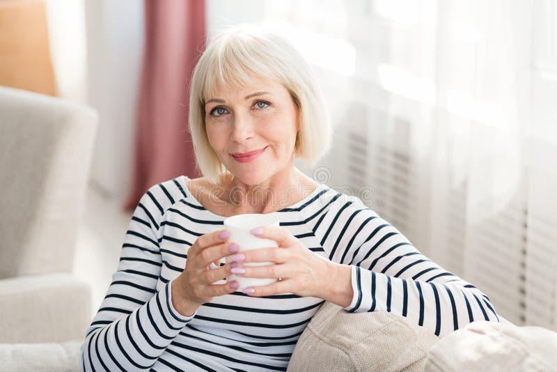 Reife Frau, die zu Hause frischen Morgenkaffee trinkt stockfotografie