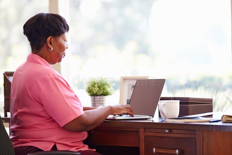 Reife Frau, die zu Hause Laptop auf Schreibtisch verwendet lizenzfreie stockfotografie