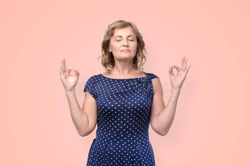 Reife Frau fühlt sich, versucht sich zu konzentrieren entspannt, oder fokussiert zu werden, schließt Augen, genießt Ruhe lizenzfreies stockbild