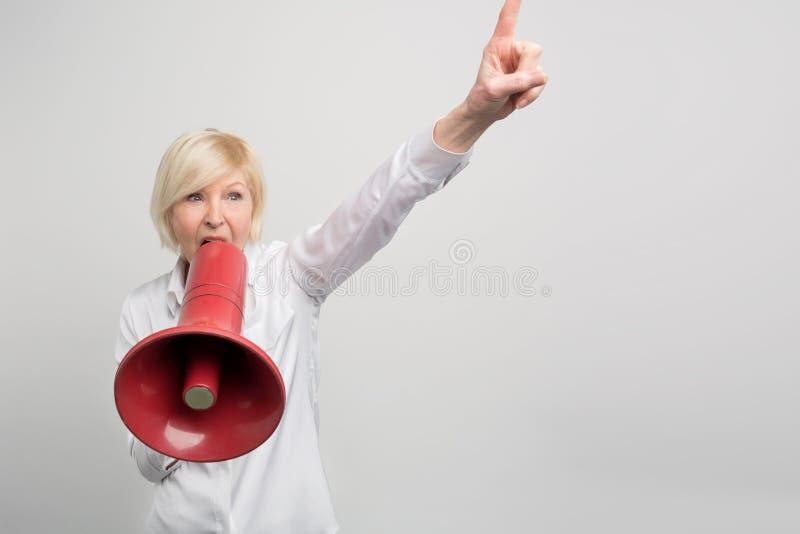 Reife Frau hält ein Megaphon nah an ihrem Mund und sreaming in ihn Sie verteidigt Menschenrechte Auf lizenzfreie stockfotos