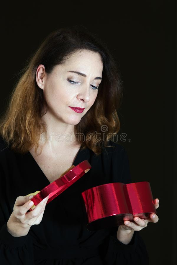 Reife Frau in ihrem 40s, einen Präsentkarton öffnend und erwartungsvoll schauen, durchdacht stockfoto