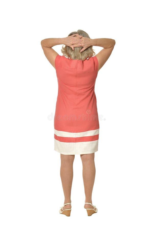 Reife Frau im rosa Kleid stockbild