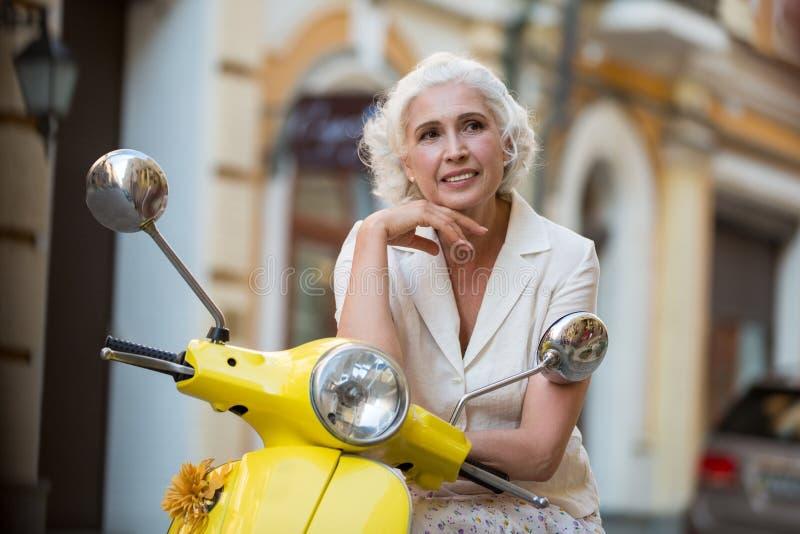 Reife Frau lehnt sich auf Roller stockfotos