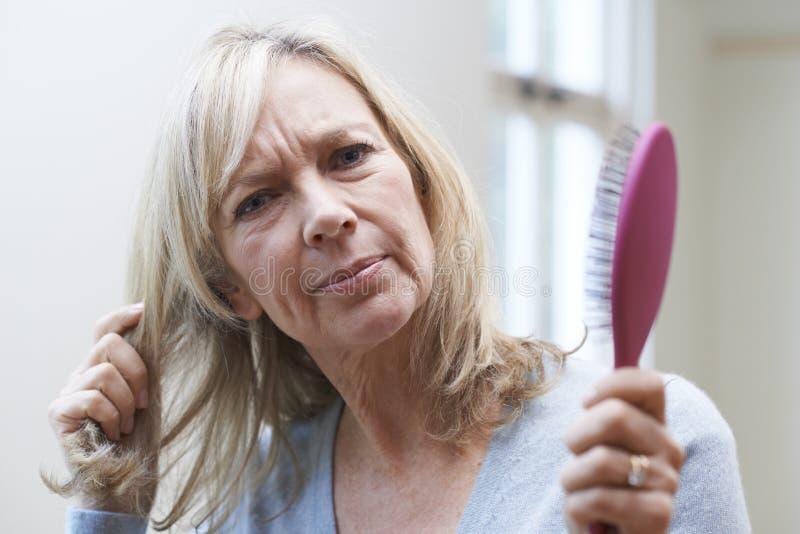 Reife Frau mit Bürste Corncerned über Haarausfall lizenzfreie stockfotografie