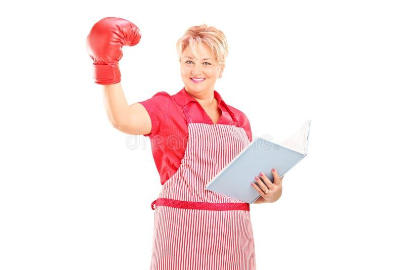 Reife Frau mit dem Boxhandschuh, der ein Notizbuch hält lizenzfreie stockfotos