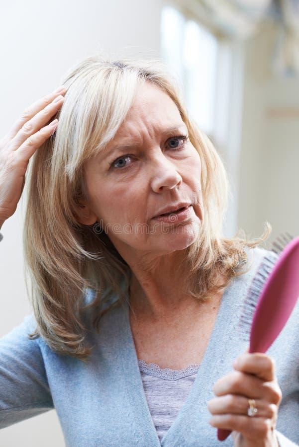 Reife Frau mit der Bürste betroffen über Haarausfall stockfotografie