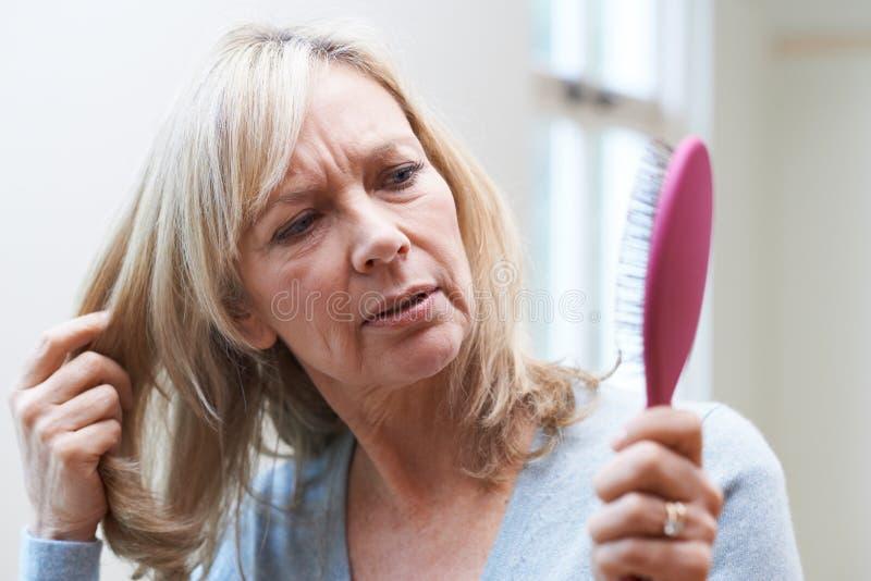Reife Frau mit der Bürste betroffen über Haarausfall stockbild