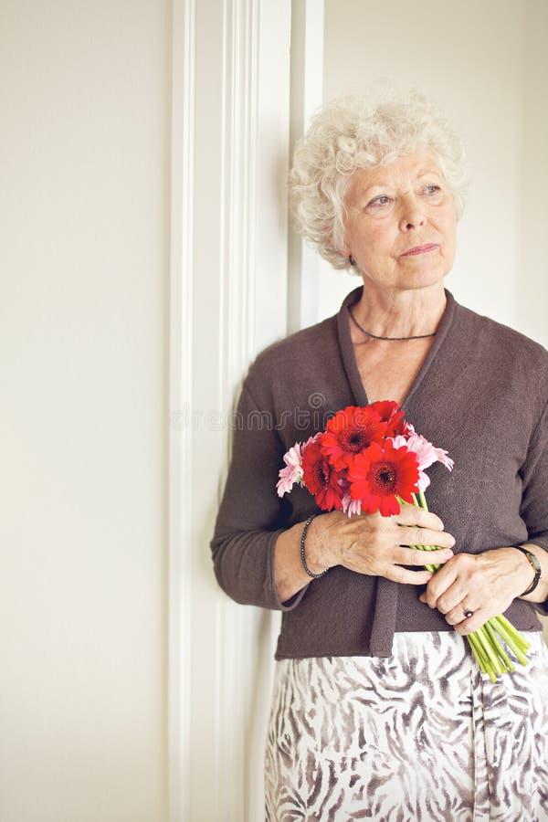 Reife Frau mit der Blumen-Aufstellung lizenzfreies stockfoto