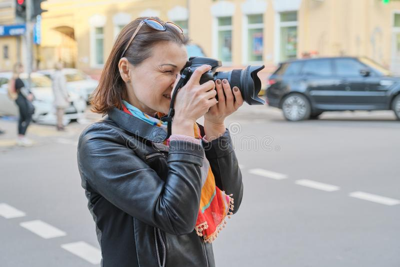 Reife Frau mit Fotokamera fotografierend auf der Straße der Frühlingsstadt, weiblicher Berufsfotograf, Kopienraum stockbilder