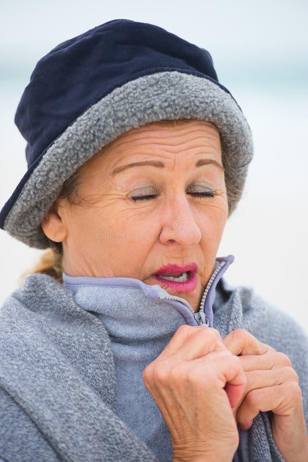 Reife Frau mit Grippe im warmen Pullover im Freien lizenzfreie stockfotografie