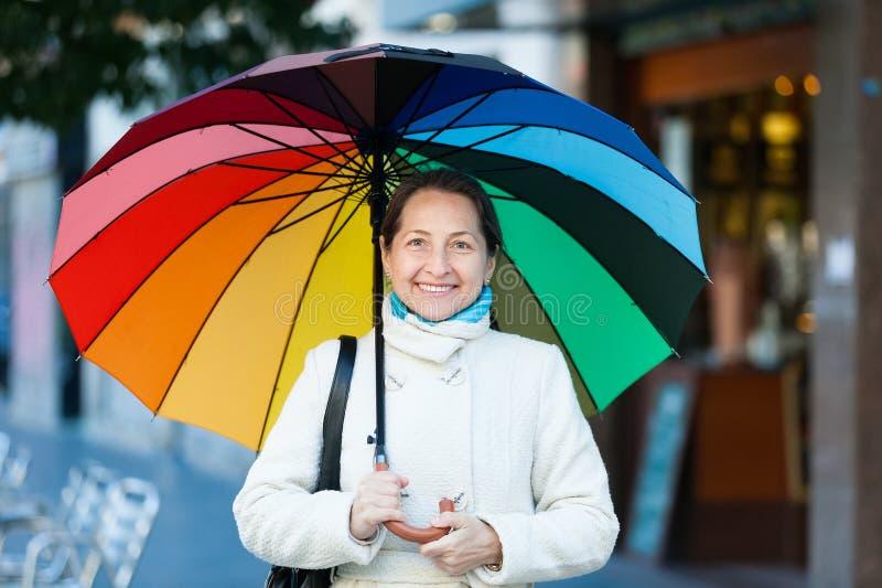 Reife Frau mit Regenschirm stockfotografie