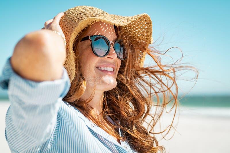 Reife Frau mit Strandhut und -Sonnenbrille lizenzfreie stockbilder