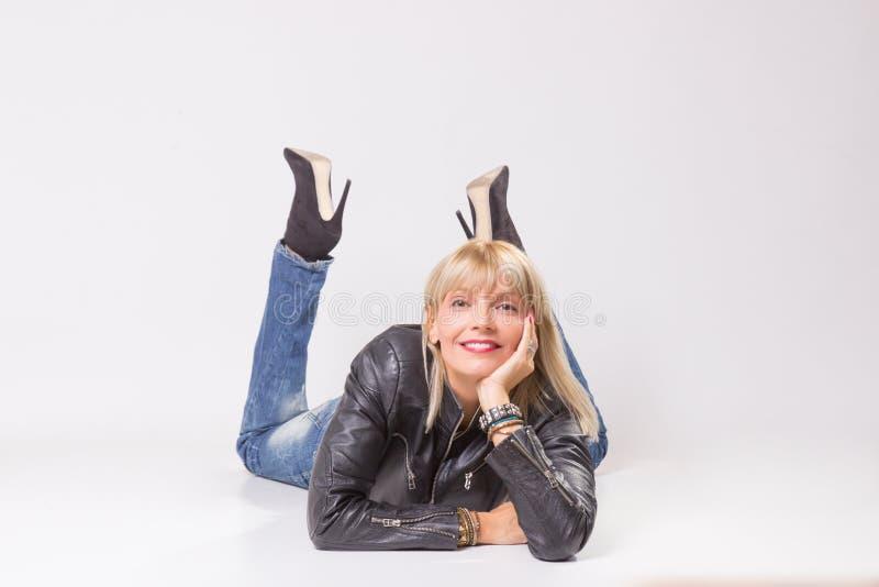 Reife Frau 40s, die auf dem Boden, Kamera betrachtend liegt stockbild