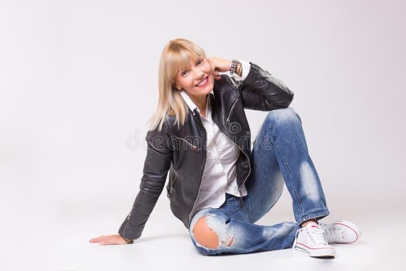 Reife Frau 40s, die das glückliche Lächeln der zufälligen Kleidung sitzt stockfoto
