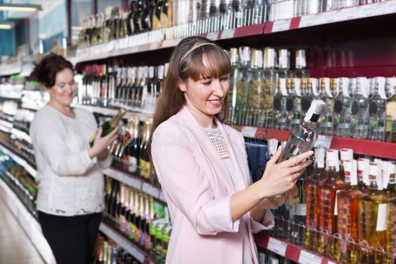 Reife Frau und ihre erwachsene Tochter, die starken Alkohol kauft stockfoto