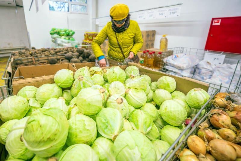 Reife Frau wählt rote Rüben in einem Gemüsegeschäft lizenzfreie stockfotos