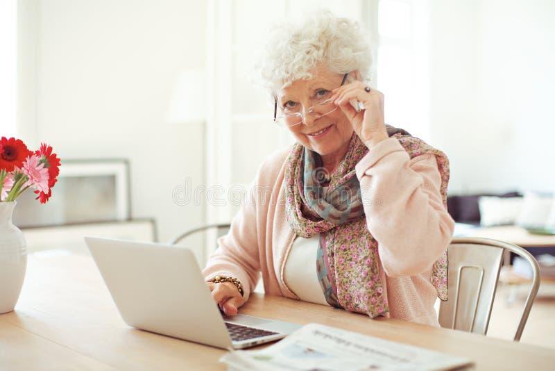 Reife Frau zu Hause unter Verwendung des Laptops lizenzfreie stockfotografie