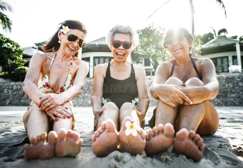 Reife Frauen, die auf dem Strand sich bräunen stockbild