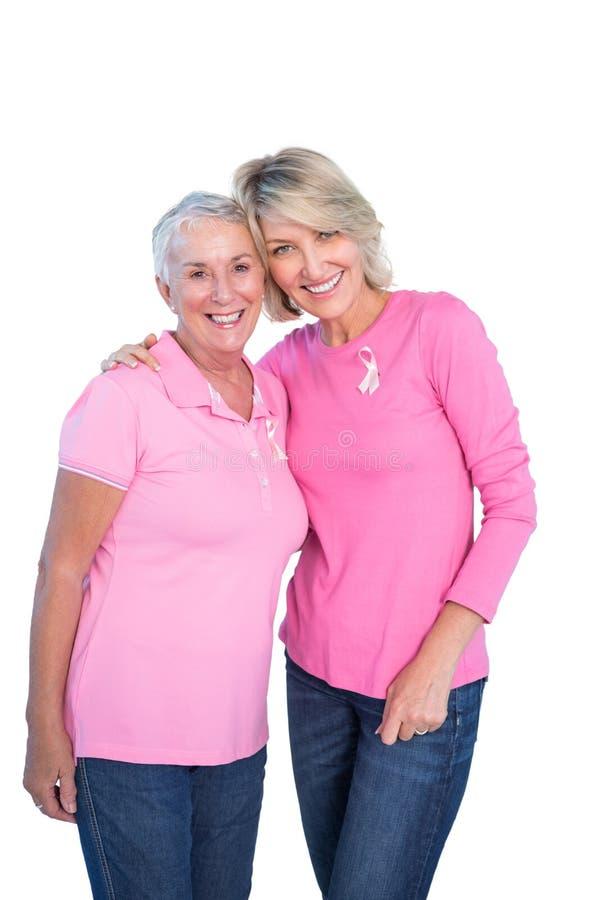Reife Frauen, die rosa Oberteile- und Brustkrebsbänder tragen stockbilder