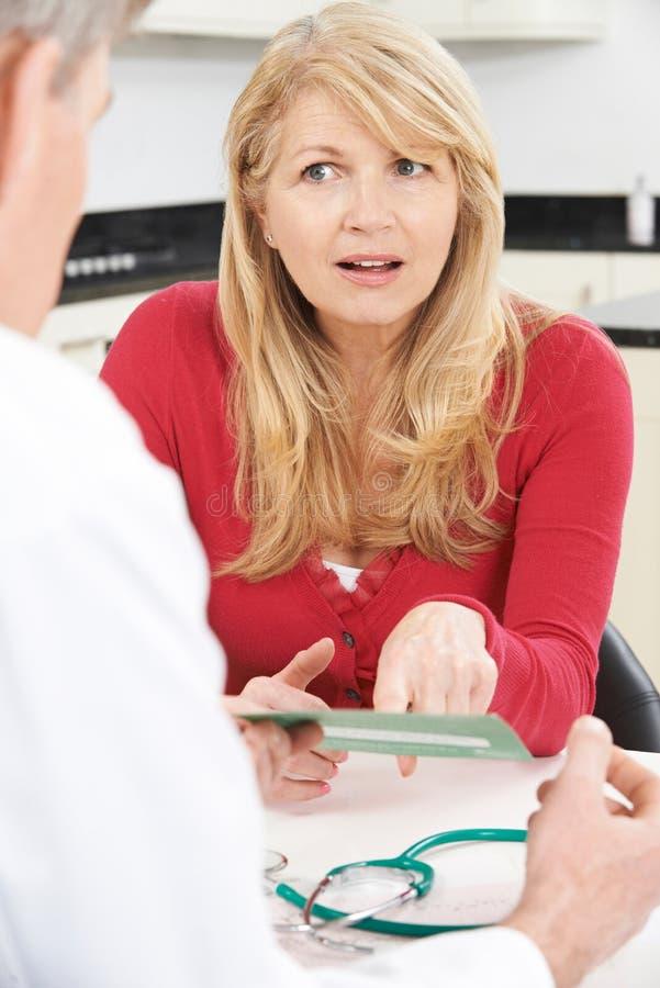 Reife Frauen-Lesebroschüre in Doktor ` s Chirurgie stockfotos