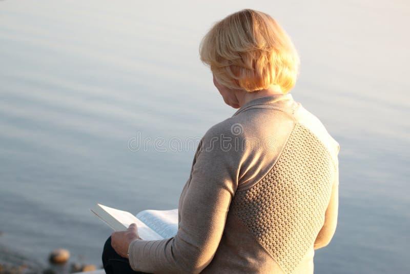 Reife Frauenlesebibel an Strand 2 stockbild