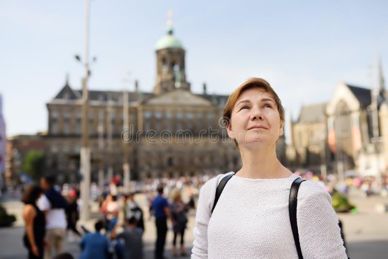Reife Frauenstellung an einem sonnigen Herbsttag im zentralen Verdammungsquadrat in der alten Stadt von Amsterdam lizenzfreies stockfoto