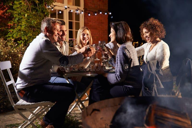 Reife Freunde, die Abendessen im Freien um Firepit genießen stockfotografie