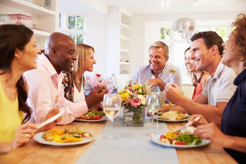 Reife Freunde, die um Tabelle am Abendessen sitzen lizenzfreies stockbild