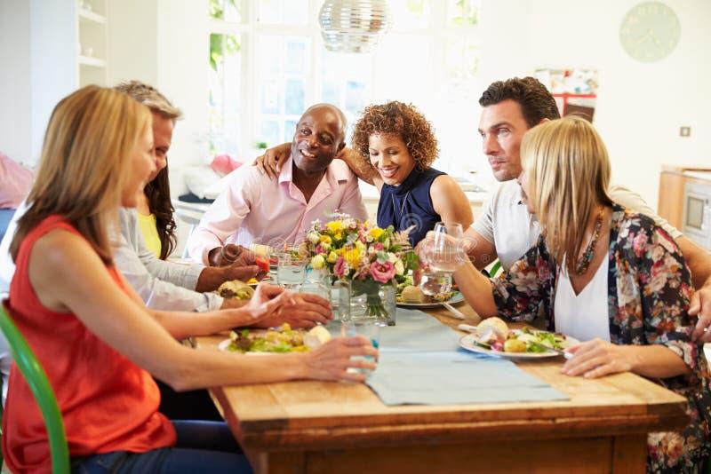 Reife Freunde, die um Tabelle am Abendessen sitzen lizenzfreies stockfoto
