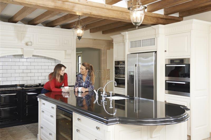 Reife Freundinnen, die in neuer Luxus gepaßter Küche stehen und lizenzfreies stockbild