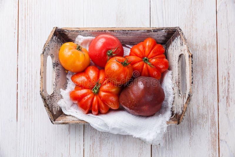 Reife frische bunte Tomaten in der Holzkiste lizenzfreie stockfotografie
