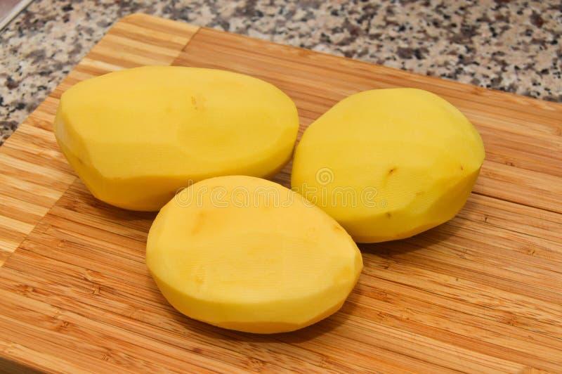 Reife frische und abgezogene Kartoffeln lizenzfreie stockfotografie
