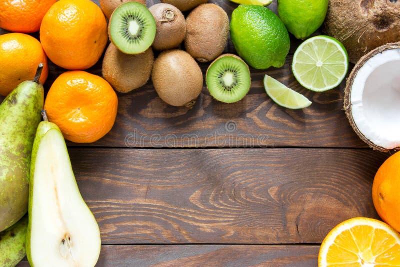 Reife Fruchtbirnenkiwikalk-Mandarinekokosnuß auf einem Holztisch mit Platz für Aufschrift stockfotografie