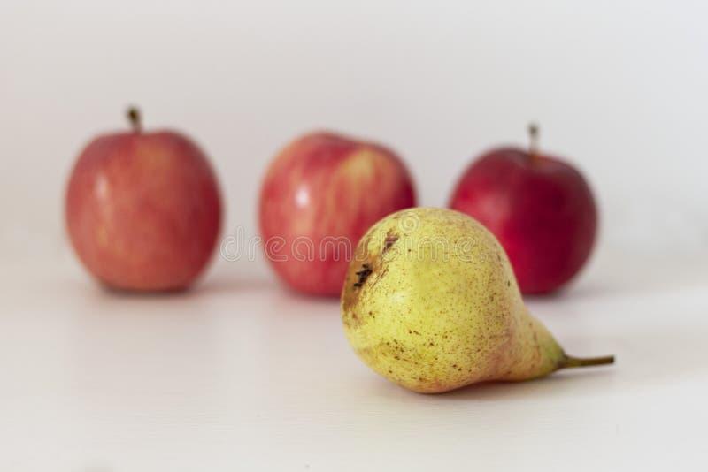 Reife gelbe Birne und rote Äpfel auf einer Tabelle auf einem weißen Hintergrund stockbilder