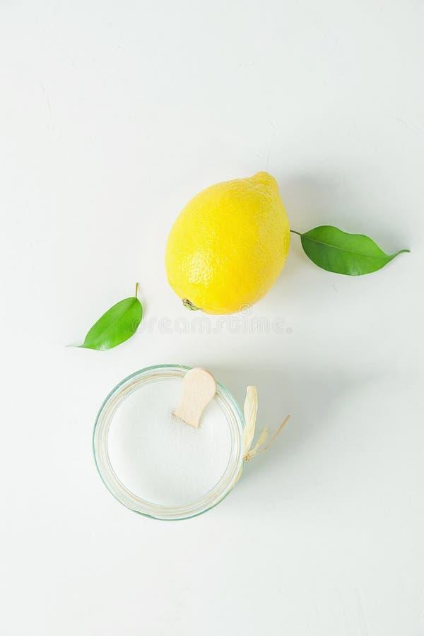 Reife gelbe Zitronen-Grün-Zitrusfrucht lässt Zucker im Glasgefäß Bestandteile für Gesicht scheuern sich auf weißem konkretem Stei stockfotos