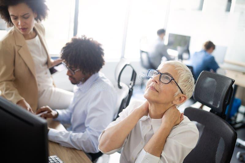 Reife Geschäftsfrau, die Druck und Kopfschmerzen im Büro hat stockbild