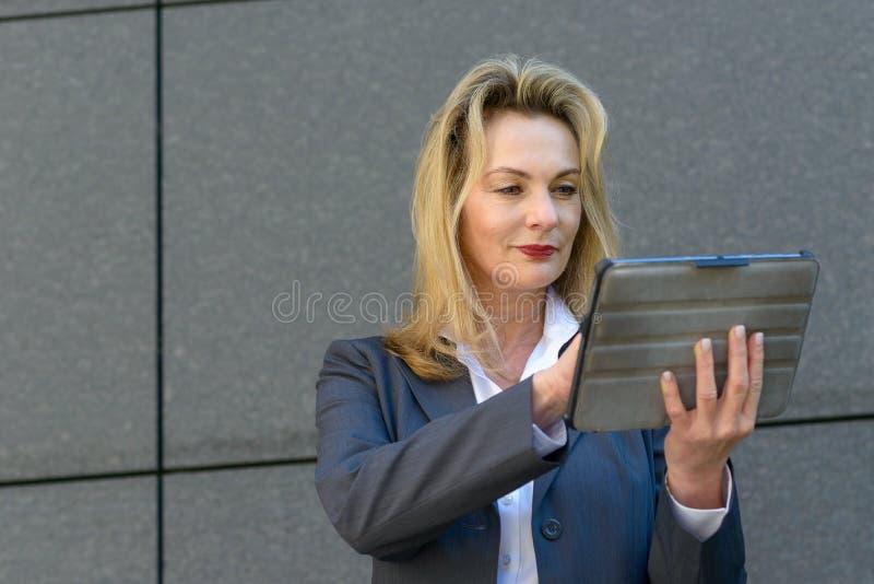 Reife Geschäftsfrau, die eine Handtablette verwendet lizenzfreies stockbild