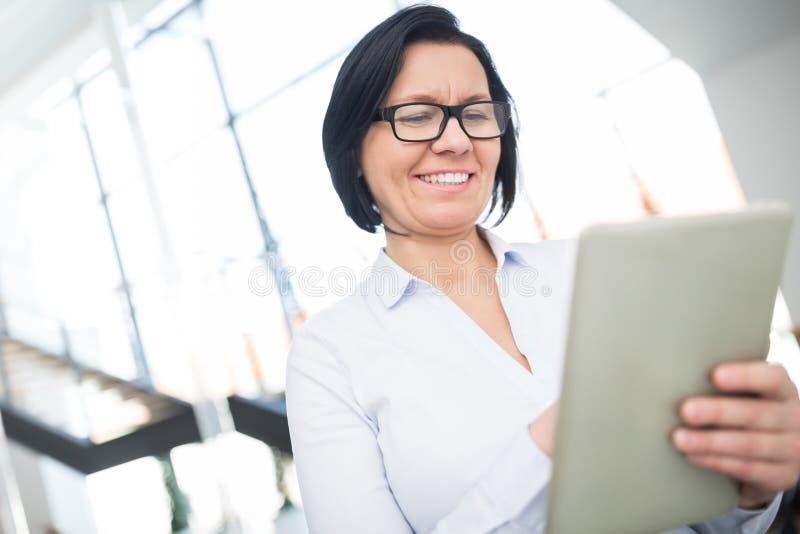Reife Geschäftsfrau Holding Digital Tablet im Büro lizenzfreies stockbild