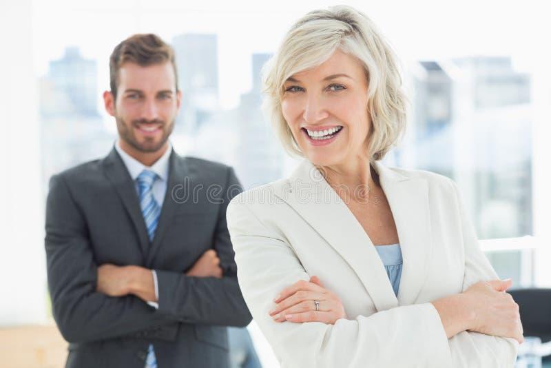 Reife Geschäftsfrau und junger Mann mit den Armen gekreuzt stockbilder