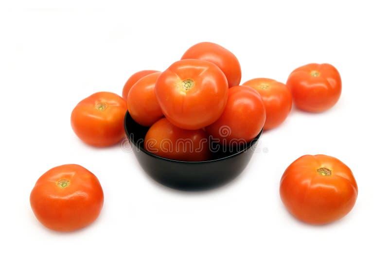 Reife geschmackvolle Tomaten in der schwarzen Schüssel auf Weiß stockfotos