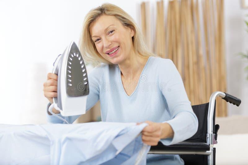 Reife glückliche Fraueneisenkleidung lizenzfreies stockbild